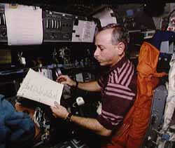 Carl reading checklists on the flight deck.  Click here for a NASA site with more pictures from this mission.